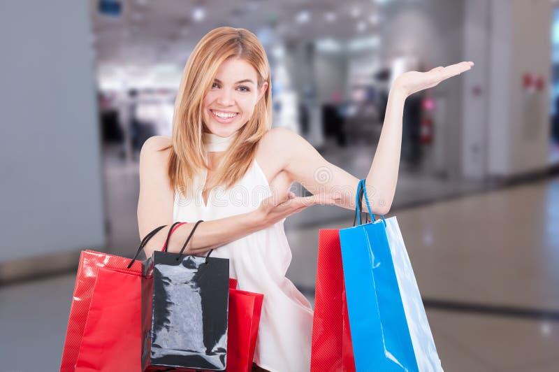 Winkelende vrouw die iets met open handpalm tonen stock foto