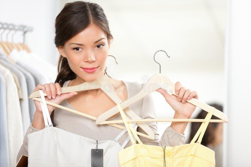 Winkelende vrouw die kleren probeert stock afbeeldingen