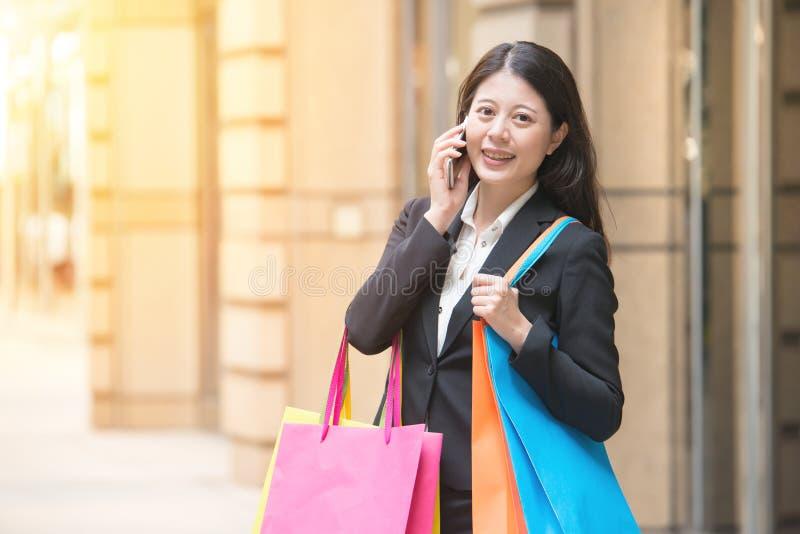 Winkelende vrouw die smartphone in stad gebruikt royalty-vrije stock afbeelding