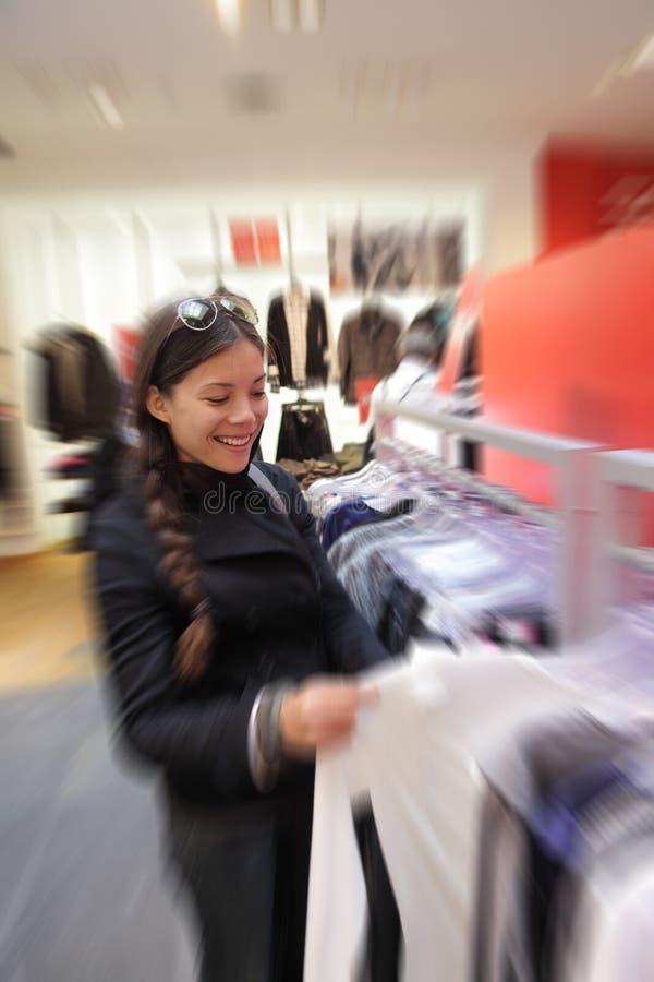 Winkelende vrouw in klerenopslag stock afbeeldingen
