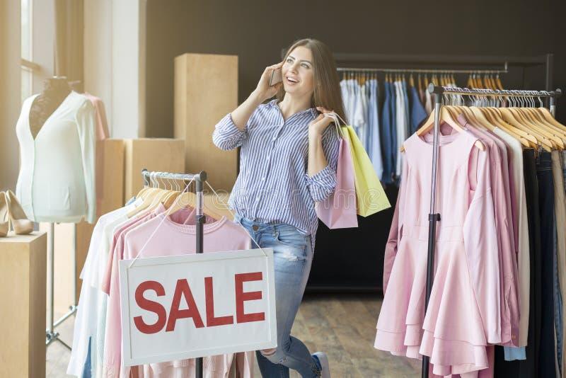 Winkelende vrouw met zakken die op de telefoon spreken stock fotografie