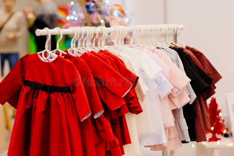 Winkelhanger met nieuwe meisjeskleding in manieropslag royalty-vrije stock fotografie