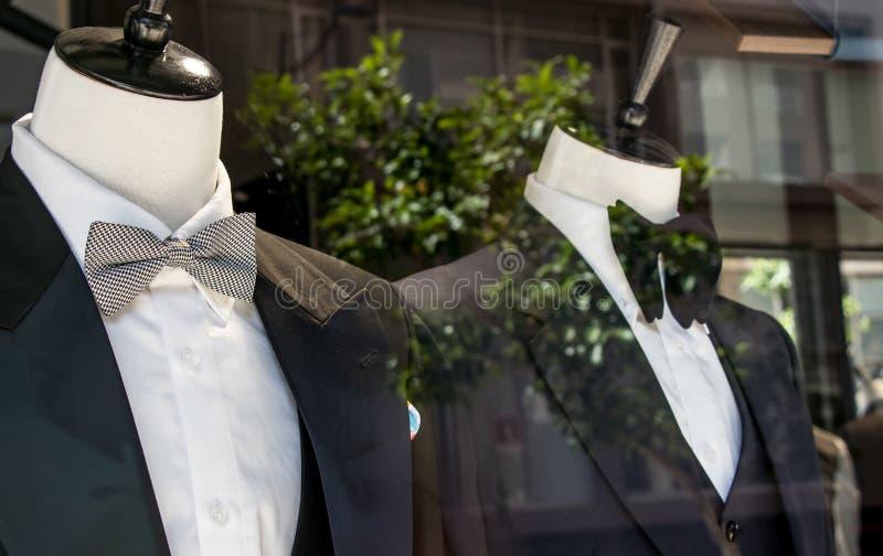 Winkelvenster van de kleermakerswinkel die van mensen 2 ledenpoppen in smokingen tonen stock foto