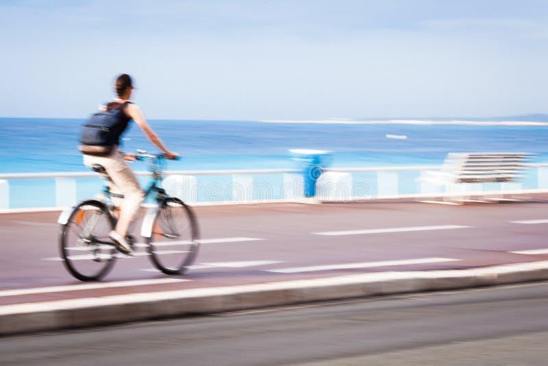 Winken Sie den unscharfen Radfahrer zu, der schnell auf einen Stadtradweg geht stockfoto