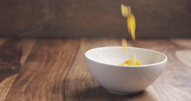 Winken Sie die unscharfen Corn Flakes zu, die in weiße Schüssel auf Holztisch fallen stockfotografie