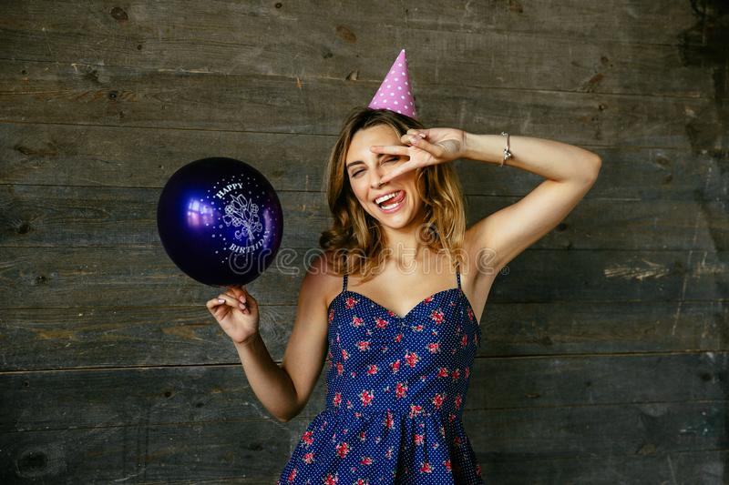 Happy woman celebrating her birthday, showing peace sign. Winking beautiful funny celebrating birthday, showing peace gesture, holds a balloon. Wearing dress stock image