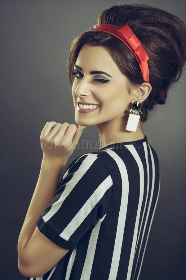 Winking enticing woman. Beautiful persuasive lady tempting with retro sixties fashion style. Enticing smiling young woman in striped attire, red headband and royalty free stock photography