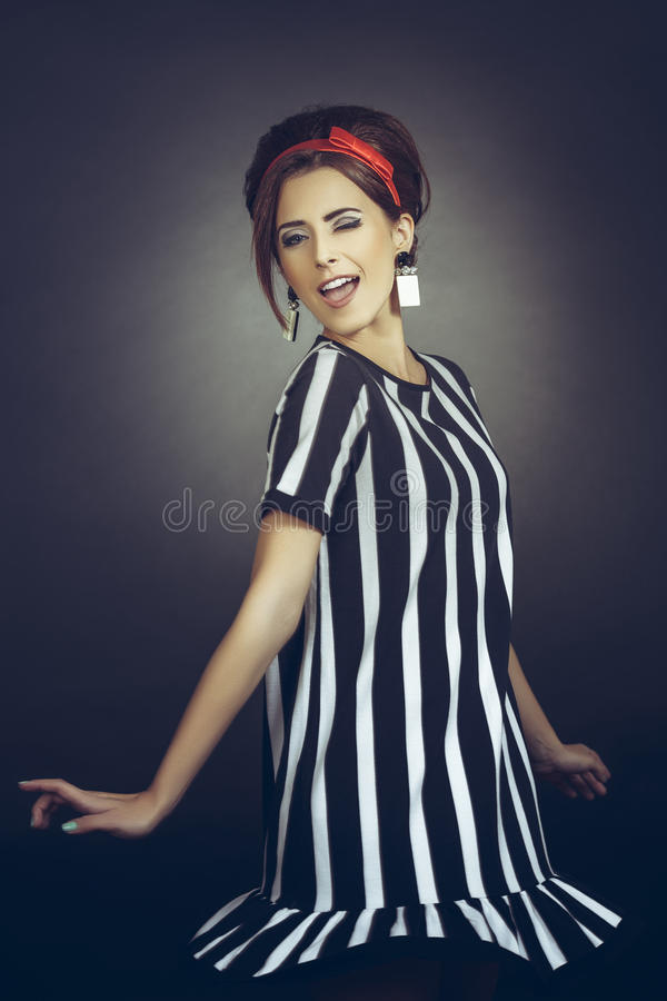 Winking flirtatious retro lady. Flirtatious alluring young lady dressed in classy retro style, winking, having fun and spinning around against dark background royalty free stock photography