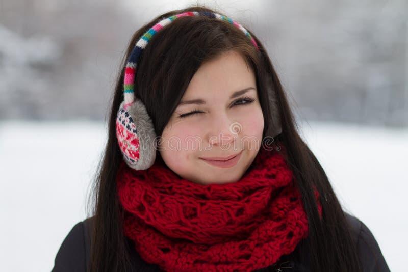 Winking girl in earplugs stock photo