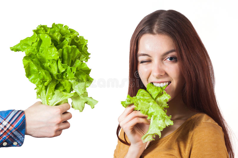 Winking girl with lettuce. Winking girl eat lettuce and hand hold a bouqet of it. Isolated background royalty free stock photo