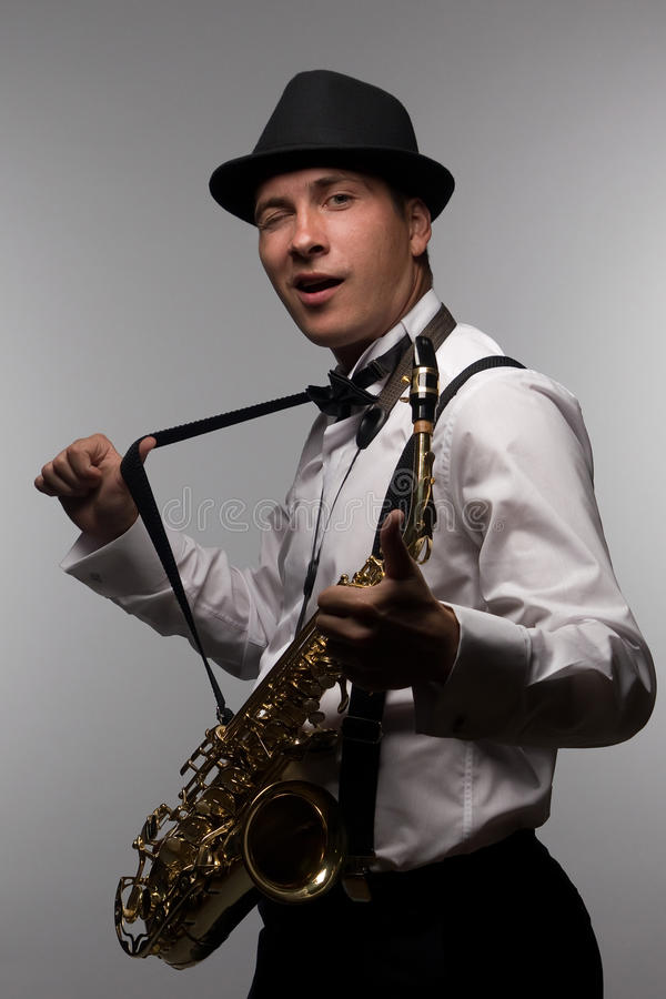 Winking saxophone player. Portrait of happy and winking saxophone player with hat. DJ with sax stock images
