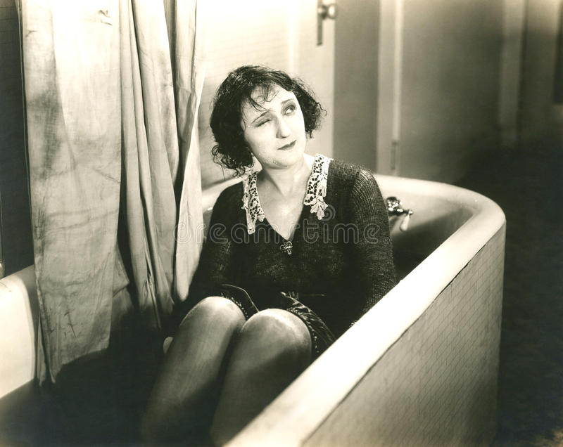 Winking woman in bathtub fully clothed royalty free stock image