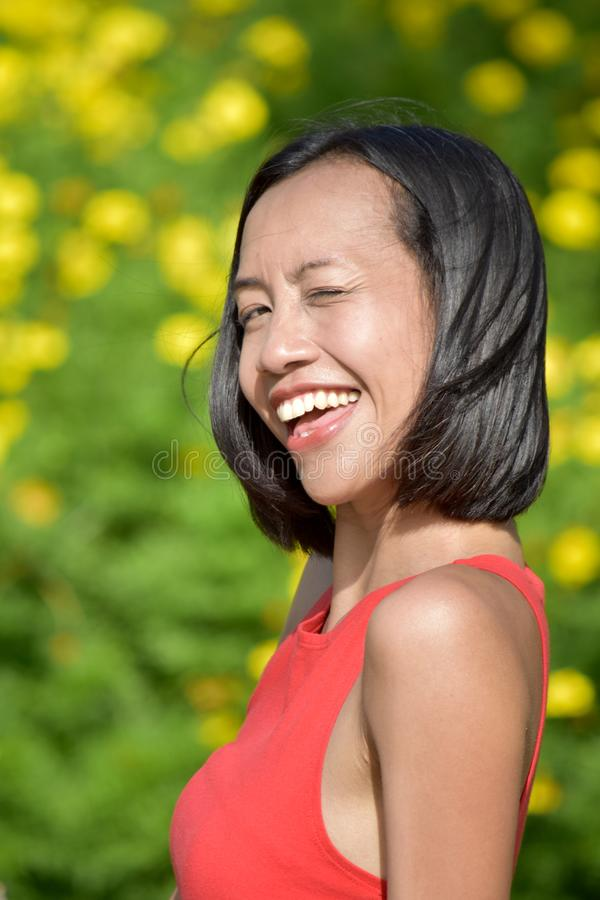 Winking Youthful Diverse Female. An attractive and asian person royalty free stock image