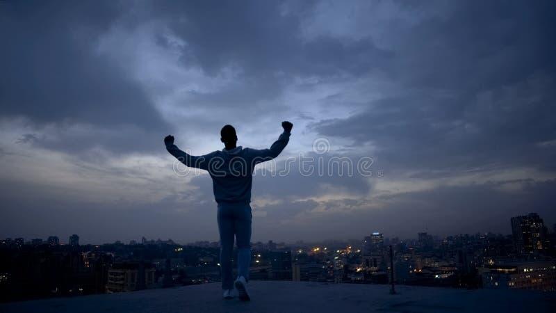 Winnaar mannelijke silhouet en nachtcityscape op achtergrond, het bereiken doelstellingen stock foto's