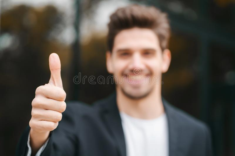 winnaar Succes De donkerbruine jonge mens in bedrijfskleding in bureaudistrict glimlacht aan camera en geeft duimen op gelukkig stock foto