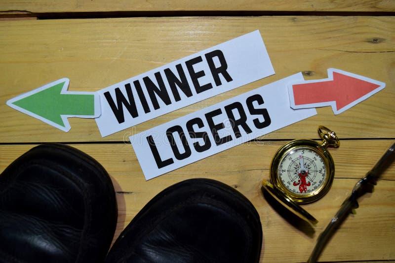 Winnaar of Verliezers tegenover richtingstekens met laarzen, oogglazen en kompas op houten stock afbeelding