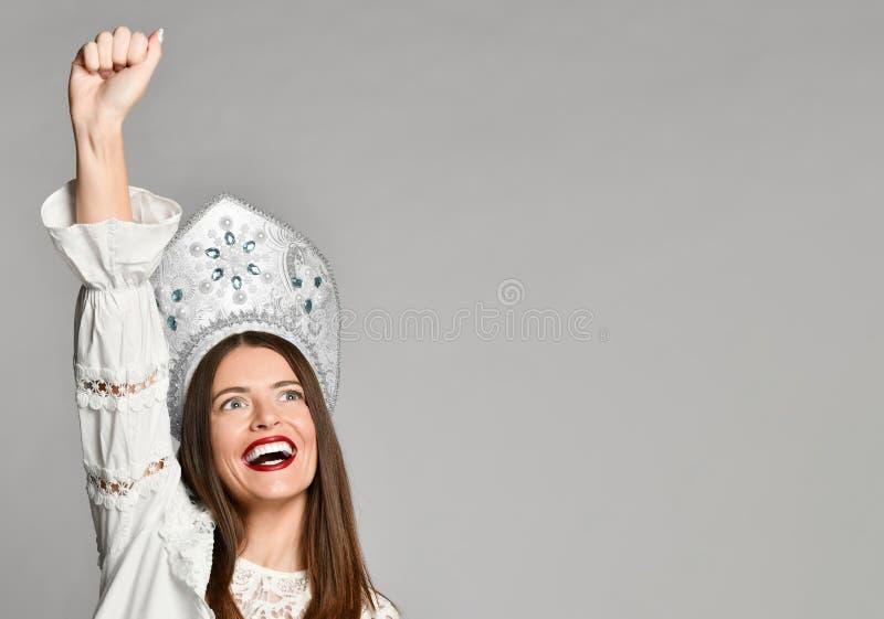 Winnaarvrouw het vieren succes op grijze achtergrond wordt geïsoleerd die stock foto