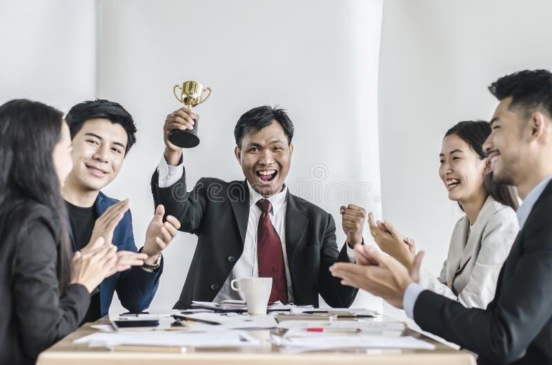Winnend commercieel team met een mensenstafmedewerker die een gouden trofee houden stock fotografie