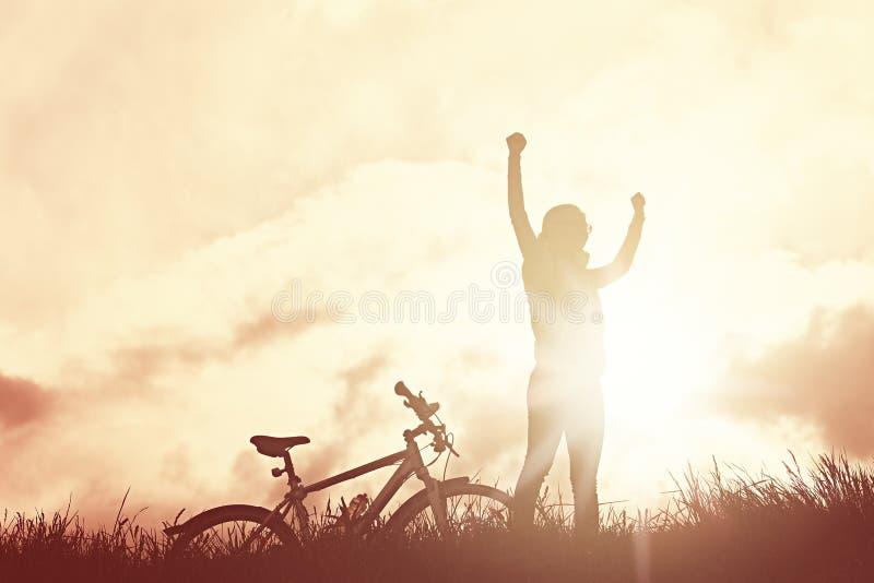 Winnend meisje met fietssilhouet royalty-vrije stock foto's