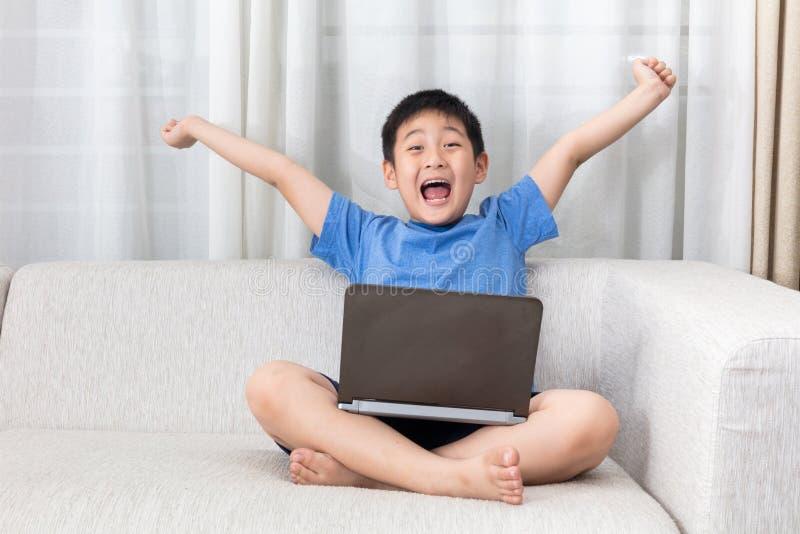 Winnende Aziatische Chinees weinig jongen die laptop op de bank met behulp van stock afbeeldingen