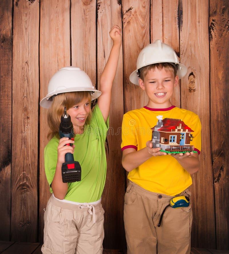 Winnende succesvolle bouwkinderen met huis modelcelebra stock foto's