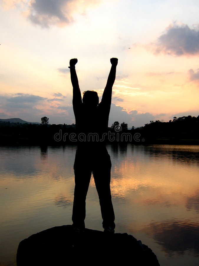 Winner. A boy strikes a winning pose after winning his competition, silhouette stock photo