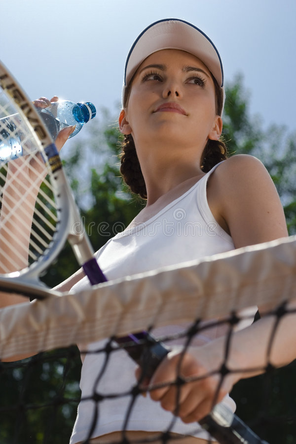 The winner. The girl-winner looks at the competitor on tennis & drink water royalty free stock images