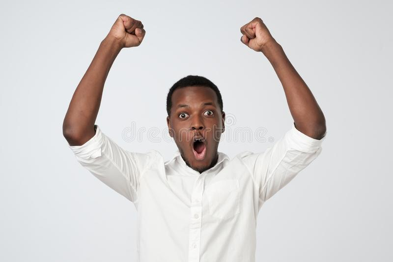 Winner celebrates. Excited african man with happy facial expression holding fists up stock images