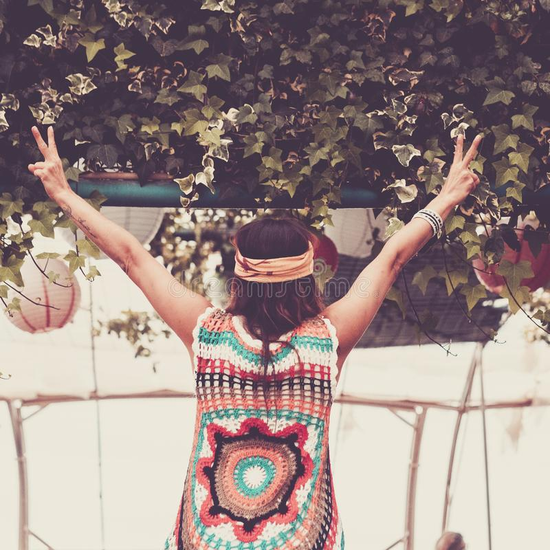 Winner concept image with freedom girl viewed from back side opening arms and opening fingers. hippy clothes like in the `60 year royalty free stock photo