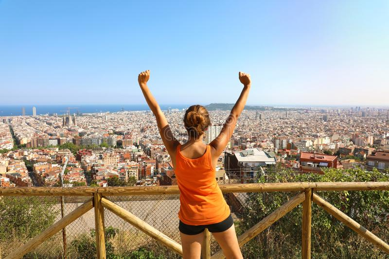 Winner fitness woman comes to the top of Barcelona and enjoying cityscape from belvedere. Excited attractive young woman in sports stock photography