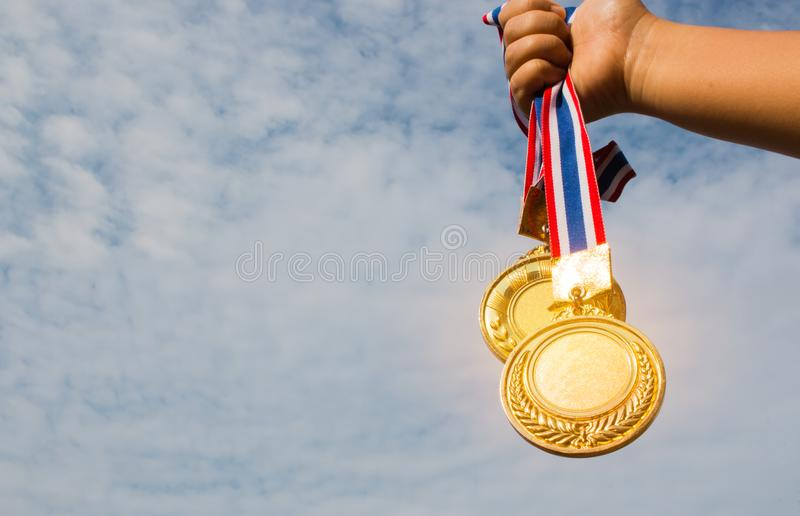 Winner hand raised and holding two gold medals with Thai ribbon royalty free stock image