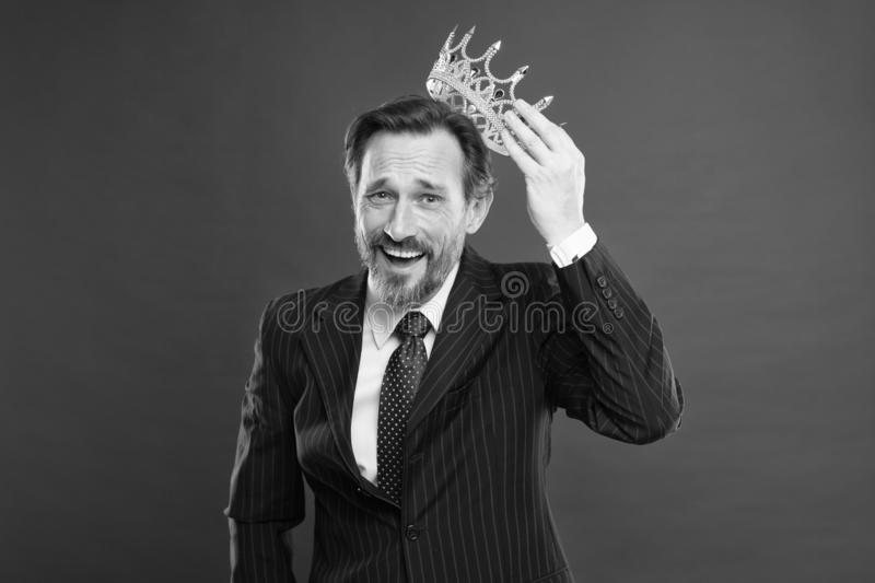 Winner at life. Successful prize winner putting crown jewel on head on red background. Best company award winner. Being stock photography