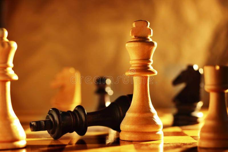Winner and loser in a game of chess. With focus to the two kings on the chessboard with one upended and one standing upright in a conceptual image royalty free stock photos