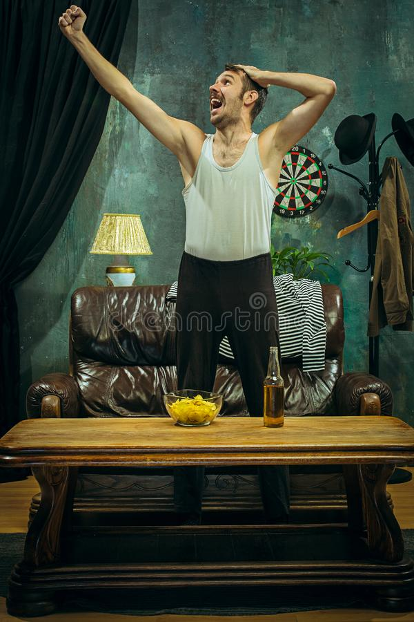 Winner. Overwhelmed cheerful man moving hands while celebrating the victory of a favourite football team stock photo