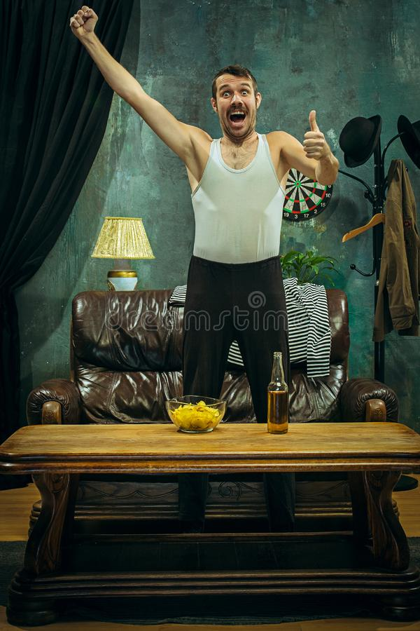 Winner. Overwhelmed cheerful man moving hands while celebrating the victory of a favourite football team royalty free stock photos