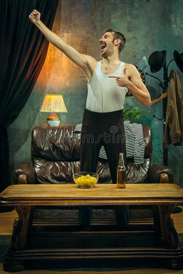 Winner. Overwhelmed cheerful man moving hands while celebrating the victory of a favourite football team royalty free stock photography