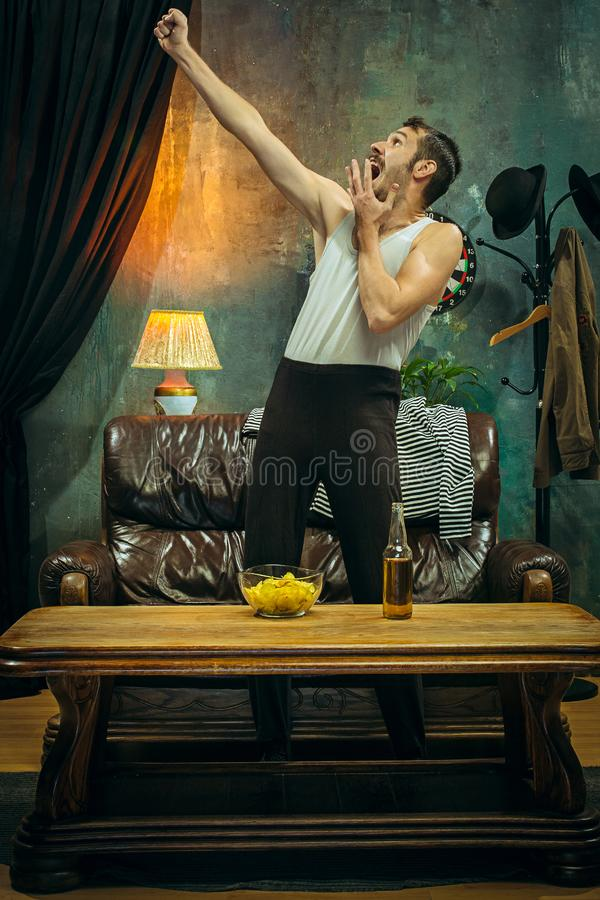 Winner. Overwhelmed cheerful man moving hands while celebrating the victory of a favourite football team stock photography