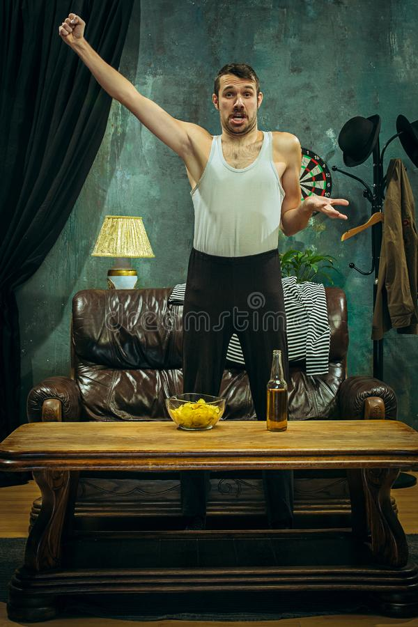 Winner. Overwhelmed cheerful man moving hands while celebrating the victory of a favourite football team royalty free stock image