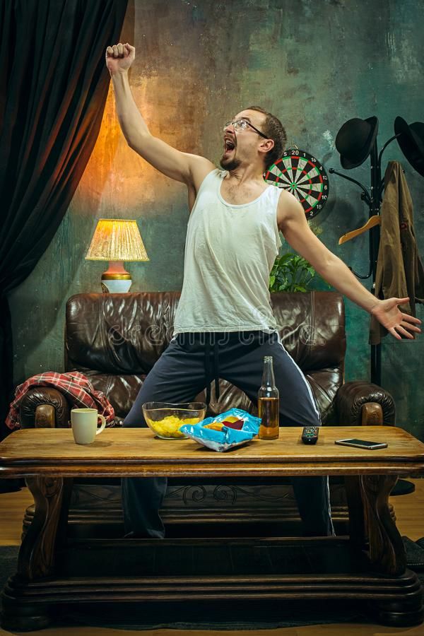 Winner. Overwhelmed cheerful man moving hands while celebrating the victory of a favourite football team royalty free stock images