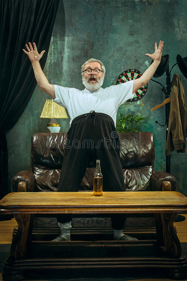 Winner. Overwhelmed cheerful man moving hands while celebrating the victory royalty free stock images