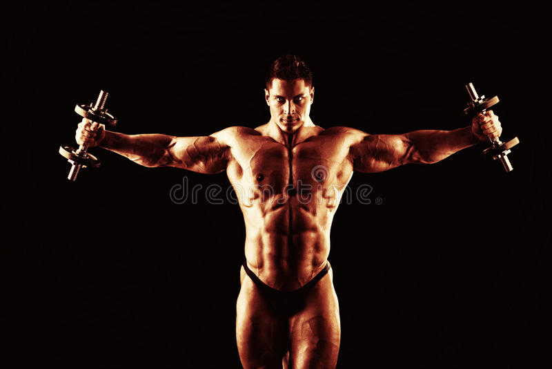 Winner. Portrait of a handsome muscular bodybuilder posing with dumbbells over black background stock photos
