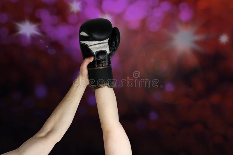 Winner's boxer hand raised in black boxing glove, closeup on dark purple background, copy space, victory concept stock photography