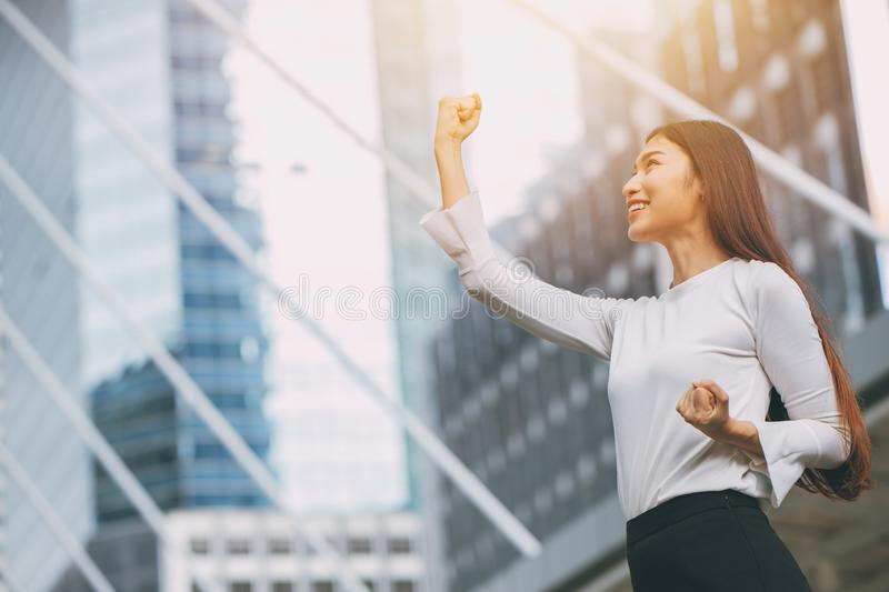 Winner successful business employee girl rise up fist hand. With city office building background royalty free stock image