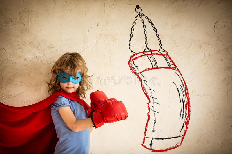 Winner. Superhero kid in red boxing gloves punching on the drawn bag. Winner and success concept royalty free stock images