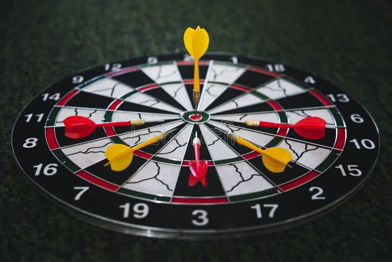 Winner yellow dart arrow hit center target of dartboard and other arrow loser metaphor marketing competition concept, on dark. Winner yellow dart arrow hit the stock photography