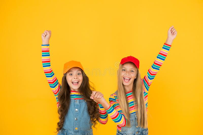 Winners reaching their goal. Excited little children making winner gestures on yellow background. Cute small winners stock images