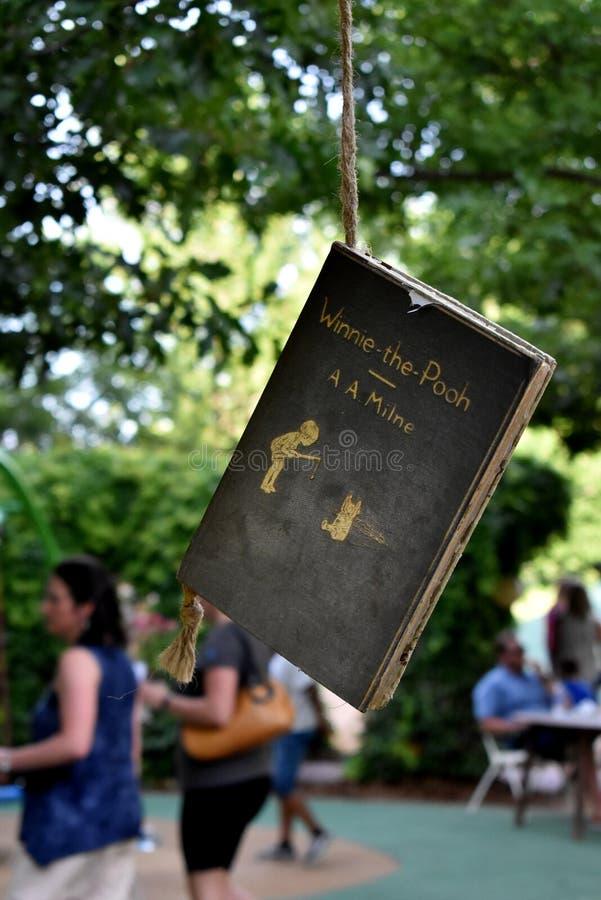 Winnie The Pooh Book Hanging en el parque imagenes de archivo