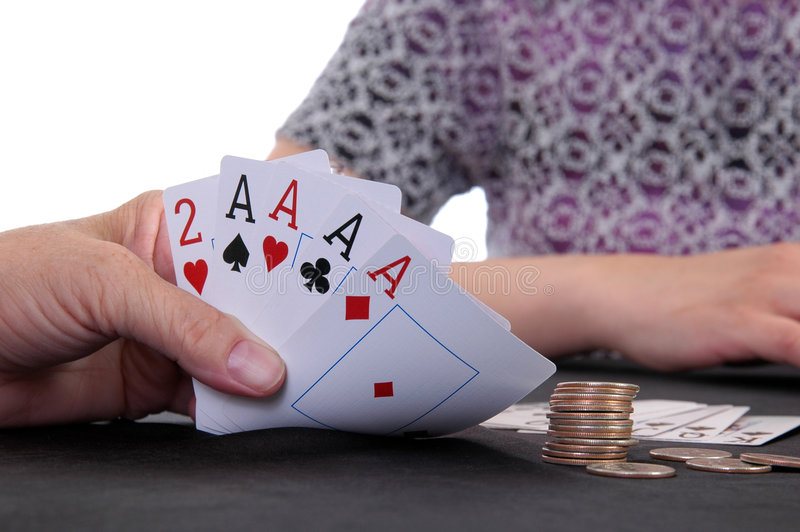 Winning. A card player folds back a winning hand royalty free stock photography
