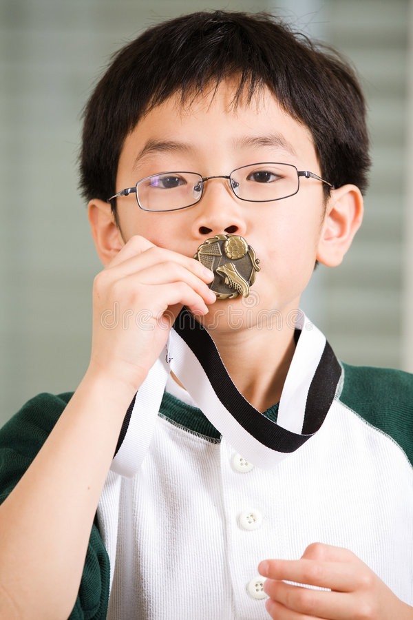 Winning boy kissing medal royalty free stock photo