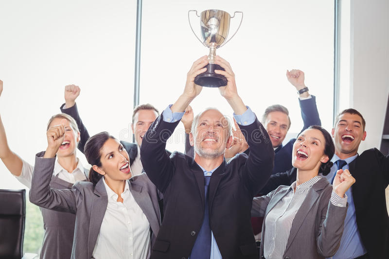 Winning business team with an executive holding trophy stock photo